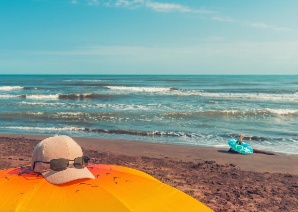 ocean, waves, sand, beach umbrella and hat