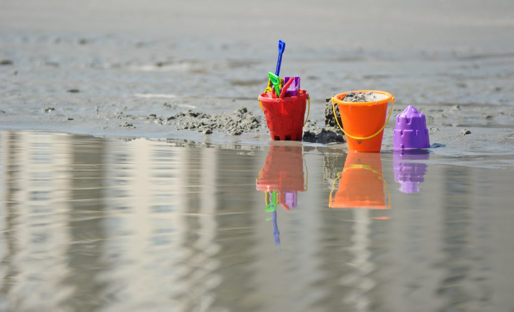 beach buckets with shovels and sand near edge of water