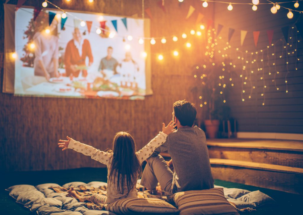 father and daughter watching a movie outside