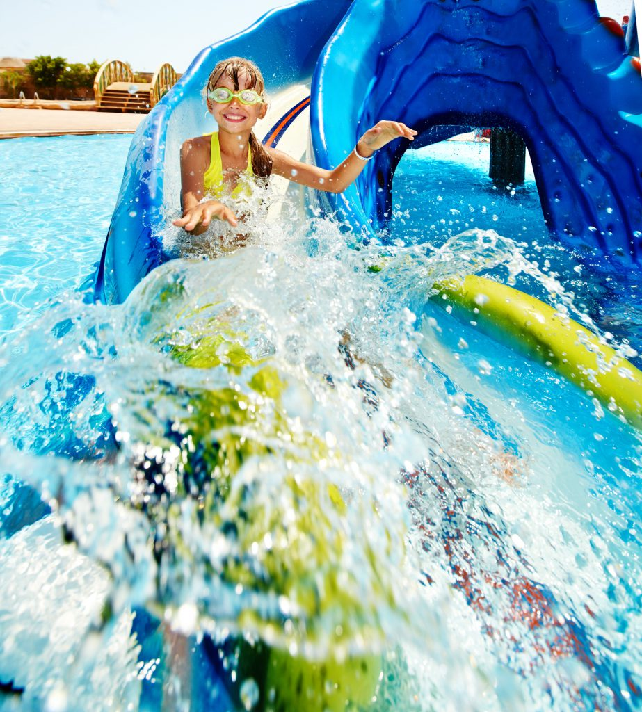 little girl on water slide at waterpark, water, wearing goggles,