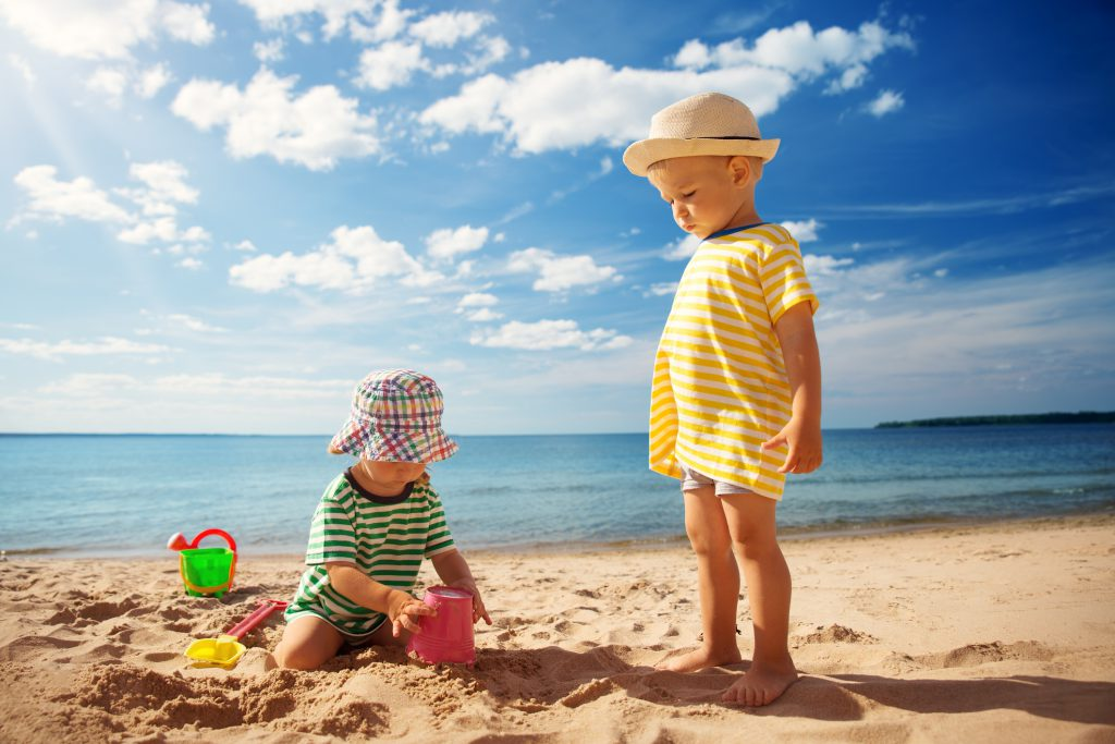 Boy and girl playing on the beach, Sand, Water, Blue sky, white clouds, beach pails, sand toys